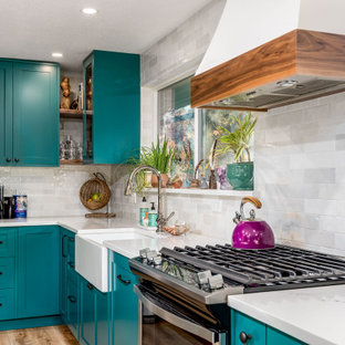 Mid-sized shabby-chic style l-shaped eat-in kitchen in Portland with a farmhouse sink, shaker cabinets, turquoise cabinets, quartz benchtops, white splashback, ceramic splashback, stainless steel appliances, laminate floors, with island, brown floor and white benchtop.
