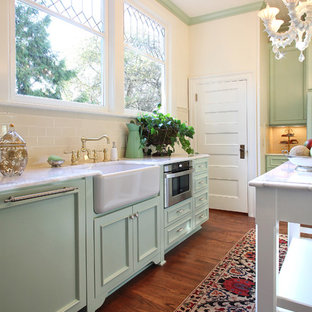 Example of a classic kitchen design in Portland with stainless steel appliances, a farmhouse sink, recessed-panel cabinets, green cabinets, quartz countertops and white backsplash