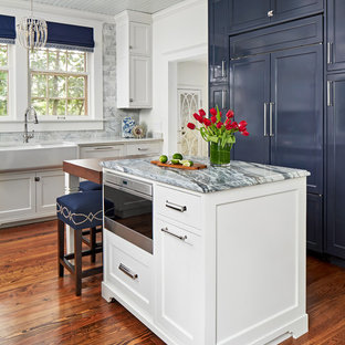 Mid-sized traditional u-shaped separate kitchen in Austin with a farmhouse sink, beaded inset cabinets, white cabinets, soapstone benchtops, multi-coloured splashback, marble splashback, panelled appliances, medium hardwood floors, with island, brown floor and white benchtop.