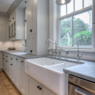 This is an example of a mid-sized traditional u-shaped eat-in kitchen in New York with a farmhouse sink, shaker cabinets, grey cabinets, soapstone benchtops, white splashback, timber splashback, stainless steel appliances, medium hardwood floors, no island, brown floor and multi-coloured benchtop.