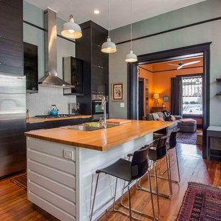 アトランタの中サイズのヴィクトリアン調のおしゃれなアイランドキッチン (ドロップインシンク、フラットパネル扉のキャビネット、木材カウンター、白いキッチンパネル、セラミックタイルのキッチンパネル、シルバーの調理設備の、無垢フローリング、濃色木目調キャビネット、オレンジの床) の写真