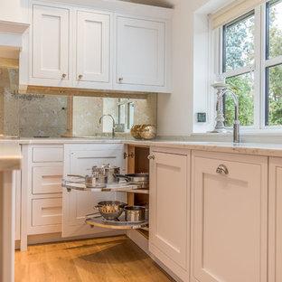 Bild på ett stort vintage kök, med en nedsänkt diskho, skåp i shakerstil, vita skåp, bänkskiva i koppar, spegel som stänkskydd, integrerade vitvaror, ljust trägolv, en köksö och gult golv