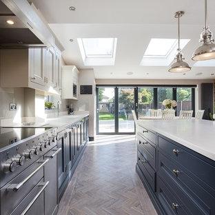 Cette photo montre une grand cuisine ouverte victorienne en L avec un placard à porte shaker, des portes de placard grises et un îlot central.