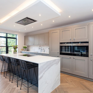 Inspiration for a medium sized contemporary single-wall kitchen/diner in London with an integrated sink, shaker cabinets, grey cabinets, quartz worktops, white splashback, marble splashback, integrated appliances and an island.