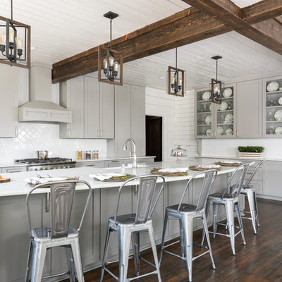 Inspiration for a farmhouse l-shaped dark wood floor and brown floor eat-in kitchen remodel in Dallas with a farmhouse sink, shaker cabinets, gray cabinets, white backsplash, stainless steel appliances and an island