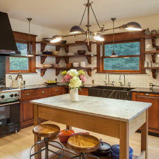 Eat-in kitchen - huge craftsman l-shaped light wood floor eat-in kitchen idea in Portland with raised-panel cabinets, soapstone countertops, white backsplash, subway tile backsplash, black appliances, an island, an integrated sink and medium tone wood cabinets