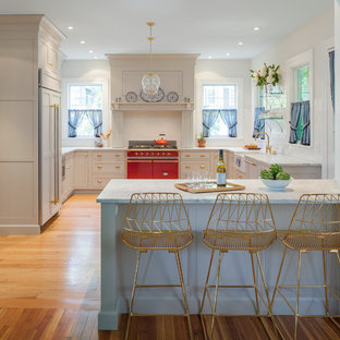 Example of a large transitional u-shaped light wood floor and brown floor eat-in kitchen design in New York with a farmhouse sink, a peninsula, recessed-panel cabinets, white cabinets, marble countertops, white backsplash, subway tile backsplash and paneled appliances