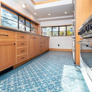 ポートランドの中サイズのおしゃれなキッチン (一体型シンク、落し込みパネル扉のキャビネット、淡色木目調キャビネット、珪岩カウンター、白いキッチンパネル、サブウェイタイルのキッチンパネル、シルバーの調理設備、セメントタイルの床、アイランドなし、青い床、黒いキッチンカウンター) の写真