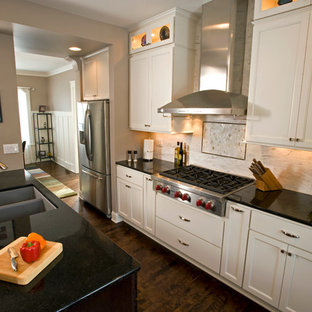 Mid-sized transitional eat-in kitchen photos - Mid-sized transitional galley dark wood floor eat-in kitchen photo in Milwaukee with an undermount sink, recessed-panel cabinets, white cabinets, quartz countertops, white backsplash, stone tile backsplash and stainless steel appliances