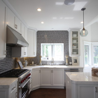 Inspiration for a large arts and crafts u-shaped eat-in kitchen in Los Angeles with a drop-in sink, shaker cabinets, white cabinets, marble benchtops, grey splashback, ceramic splashback, stainless steel appliances, dark hardwood floors and with island.