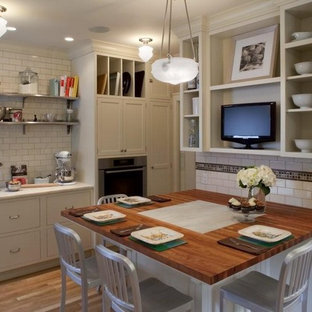 Eat-in kitchen - large craftsman u-shaped light wood floor eat-in kitchen idea in Portland with a farmhouse sink, shaker cabinets, white cabinets, marble countertops, white backsplash, subway tile backsplash, stainless steel appliances and no island