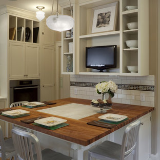 Example of a large classic u-shaped light wood floor eat-in kitchen design in Portland with white cabinets, wood countertops, a farmhouse sink, shaker cabinets, white backsplash, subway tile backsplash, stainless steel appliances and no island