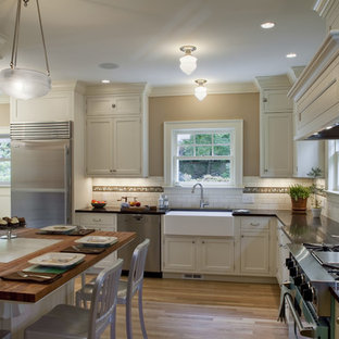 Inspiration for a large timeless u-shaped light wood floor eat-in kitchen remodel in Portland with a farmhouse sink, shaker cabinets, white cabinets, white backsplash, subway tile backsplash, stainless steel appliances and no island