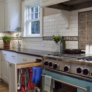 ポートランドの大きいトラディショナルスタイルのおしゃれなキッチン (クオーツストーンカウンター、カラー調理設備、シェーカースタイル扉のキャビネット、白いキャビネット、白いキッチンパネル、サブウェイタイルのキッチンパネル、淡色無垢フローリング、アイランドなし) の写真