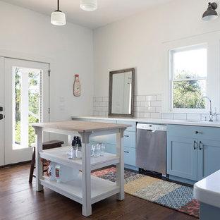 オースティンの中くらいのカントリー風おしゃれなキッチン (アンダーカウンターシンク、シェーカースタイル扉のキャビネット、青いキャビネット、クオーツストーンカウンター、黄色いキッチンパネル、サブウェイタイルのキッチンパネル、シルバーの調理設備、濃色無垢フローリング、茶色い床) の写真