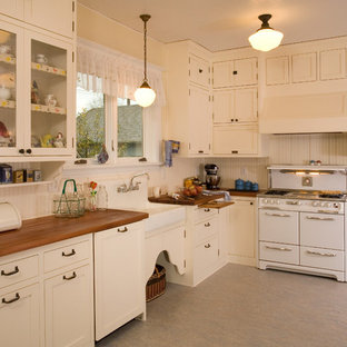 Kitchen - country kitchen idea in Seattle with a farmhouse sink, wood countertops, white cabinets, white appliances and shaker cabinets