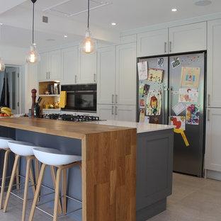 ハートフォードシャーのコンテンポラリースタイルのダイニングキッチンの画像 (シェーカースタイル扉のキャビネット、白いキャビネット、シルバーの調理設備、アイランド1つ)