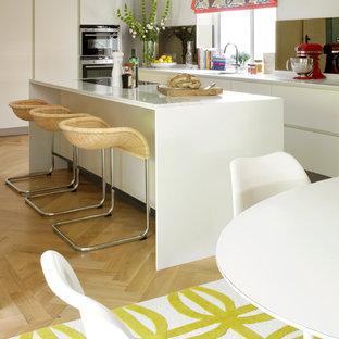 Imagen de cocina comedor clásica renovada, de tamaño medio, con armarios con paneles lisos, puertas de armario blancas, salpicadero con efecto espejo, electrodomésticos de acero inoxidable, suelo de madera clara y una isla
