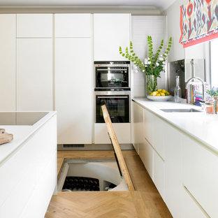 Esempio di una cucina contemporanea di medie dimensioni con lavello sottopiano, ante lisce, ante bianche, elettrodomestici da incasso, parquet chiaro e isola