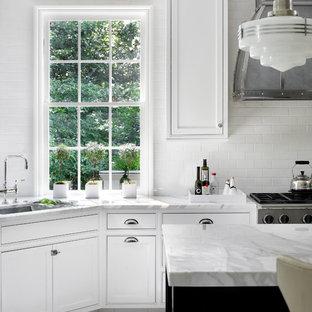 Modelo de cocina clásica con armarios con rebordes decorativos y suelo de madera pintada