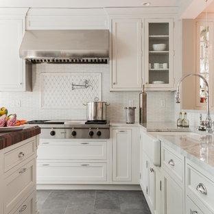 Modelo de cocina tradicional con fregadero sobremueble, armarios con paneles empotrados, puertas de armario blancas, salpicadero blanco, electrodomésticos de acero inoxidable, suelo de pizarra y suelo gris