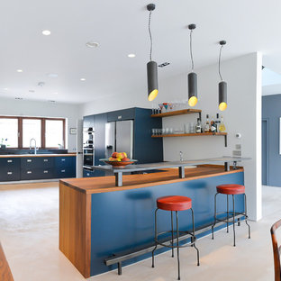 Example of a mid-sized trendy l-shaped concrete floor open concept kitchen design in Sussex with a drop-in sink, flat-panel cabinets, blue cabinets, wood countertops, black backsplash, ceramic backsplash, an island and stainless steel appliances