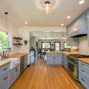 Large transitional kitchen designs - Large transitional galley light wood floor kitchen photo in Portland with a farmhouse sink, recessed-panel cabinets, blue cabinets, wood countertops, white backsplash, subway tile backsplash, stainless steel appliances and a peninsula