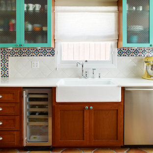 Tuscan kitchen photo in Los Angeles with a farmhouse sink, glass-front cabinets, quartz countertops, multicolored backsplash, stainless steel appliances and dark wood cabinets