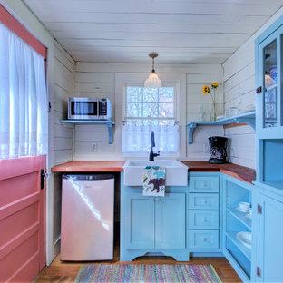 リトルロックのシャビーシック調のおしゃれなL型キッチン (エプロンフロントシンク、シェーカースタイル扉のキャビネット、青いキャビネット、木材カウンター、白いキッチンパネル、無垢フローリング、アイランドなし、茶色い床、茶色いキッチンカウンター、塗装板張りの天井) の写真