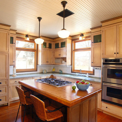 Inspiration for a craftsman l-shaped medium tone wood floor enclosed kitchen remodel in Minneapolis with an undermount sink, shaker cabinets, light wood cabinets, granite countertops, white backsplash, subway tile backsplash, stainless steel appliances and an island