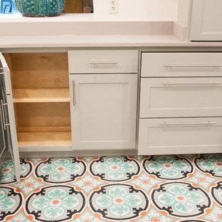 オースティンの中くらいの地中海スタイルのおしゃれな独立型キッチン (シングルシンク、シェーカースタイル扉のキャビネット、クオーツストーンカウンター、セメントタイルの床、緑のキャビネット、ベージュキッチンパネル、シルバーの調理設備、アイランドなし) の写真