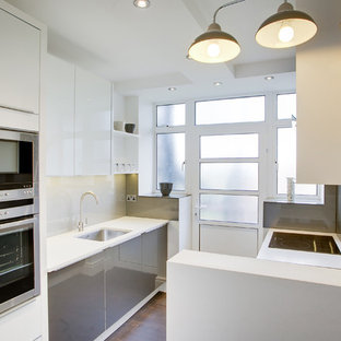 Small contemporary enclosed kitchen ideas - Small trendy galley medium tone wood floor enclosed kitchen photo in West Midlands with a single-bowl sink, flat-panel cabinets, white cabinets, concrete countertops, white backsplash, glass sheet backsplash, stainless steel appliances and no island