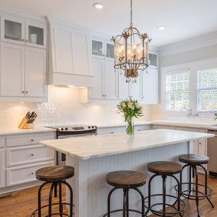 Exempel på ett klassiskt l-kök, med skåp i shakerstil, vita skåp, marmorbänkskiva, vitt stänkskydd, stänkskydd i tunnelbanekakel, rostfria vitvaror, mellanmörkt trägolv och en köksö