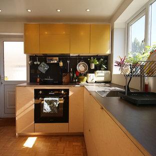 小さいエクレクティックスタイルのおしゃれなキッチン (ドロップインシンク、フラットパネル扉のキャビネット、淡色木目調キャビネット、ラミネートカウンター、黒いキッチンパネル、シルバーの調理設備の、淡色無垢フローリング、アイランドなし、グレーのキッチンカウンター) の写真