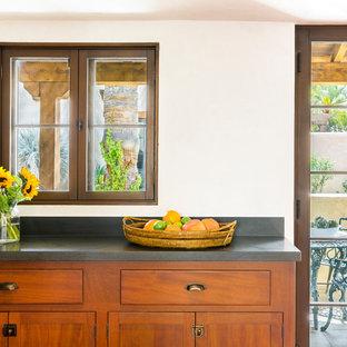 フェニックスの巨大なサンタフェスタイルのおしゃれなキッチン (アンダーカウンターシンク、シェーカースタイル扉のキャビネット、濃色木目調キャビネット、御影石カウンター、黒いキッチンパネル、石スラブのキッチンパネル、シルバーの調理設備の、コンクリートの床、赤い床、黒いキッチンカウンター) の写真