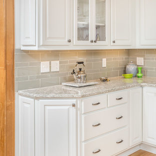 Photo of a small traditional u-shaped eat-in kitchen in Other with an undermount sink, raised-panel cabinets, white cabinets, quartz benchtops, grey splashback, glass tile splashback, stainless steel appliances, light hardwood floors and yellow floor.