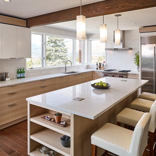 Idee per una cucina a L contemporanea con lavello sottopiano, ante lisce, ante in legno chiaro, paraspruzzi bianco, elettrodomestici in acciaio inossidabile, parquet scuro, isola, pavimento marrone e top grigio