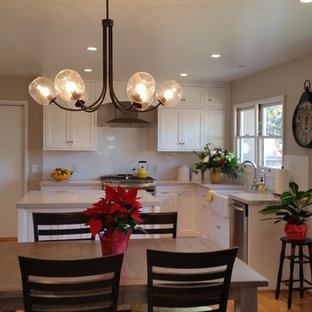 Mid-sized traditional eat-in kitchen pictures - Eat-in kitchen - mid-sized traditional u-shaped light wood floor eat-in kitchen idea in Santa Barbara with a farmhouse sink, recessed-panel cabinets, white cabinets, quartz countertops, white backsplash, cement tile backsplash, stainless steel appliances and an island