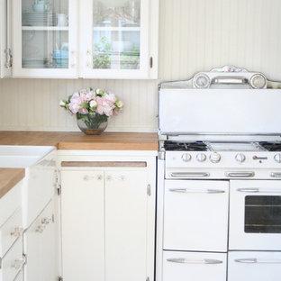 サンタバーバラの小さいシャビーシック調のおしゃれなキッチン (エプロンフロントシンク、ガラス扉のキャビネット、白いキャビネット、木材カウンター、白いキッチンパネル、シルバーの調理設備、セラミックタイルの床、アイランドなし) の写真