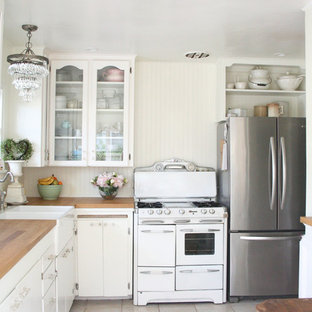 Small shabby-chic style l-shaped eat-in kitchen in Santa Barbara with a farmhouse sink, glass-front cabinets, white cabinets, wood benchtops, white splashback, stainless steel appliances, ceramic floors and no island.