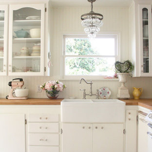 Inspiration for a shabby-chic style kitchen in Santa Barbara with a farmhouse sink, glass-front cabinets, white cabinets, wood benchtops and white splashback.
