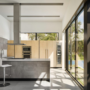 This is an example of a modern kitchen in Miami with an undermount sink, flat-panel cabinets, light wood cabinets, white splashback, panelled appliances, a peninsula and grey floor.