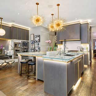 Contemporary eat-in kitchen photos - Inspiration for a contemporary u-shaped medium tone wood floor and brown floor eat-in kitchen remodel in Chicago with a double-bowl sink, flat-panel cabinets, gray cabinets, glass countertops, white backsplash and an island