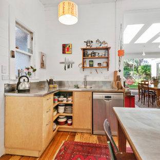 ウェリントンのエクレクティックスタイルのおしゃれなアイランドキッチン (一体型シンク、フラットパネル扉のキャビネット、中間色木目調キャビネット、ステンレスカウンター、シルバーの調理設備、無垢フローリング、茶色い床、グレーのキッチンカウンター) の写真