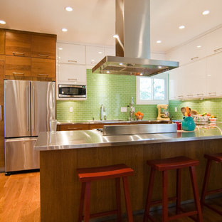Inspiration for a modern kitchen remodel in Other with flat-panel cabinets, stainless steel appliances, stainless steel countertops, medium tone wood cabinets and green backsplash