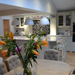 Design ideas for a medium sized contemporary single-wall kitchen/diner in Hertfordshire with a belfast sink, beaded cabinets, white cabinets, composite countertops, black splashback, ceramic splashback, black appliances, painted wood flooring and an island.