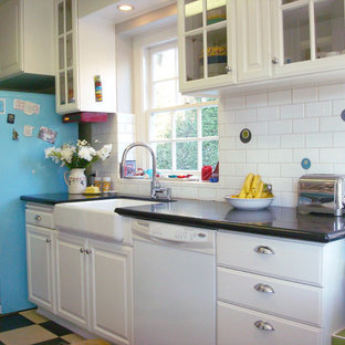 Photo of a mid-sized eclectic galley separate kitchen in Los Angeles with a farmhouse sink, white cabinets, white splashback, subway tile splashback, coloured appliances, glass-front cabinets, vinyl floors, quartz benchtops and no island.