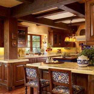 フェニックスの大きい地中海スタイルのおしゃれなキッチン (ダブルシンク、レイズドパネル扉のキャビネット、中間色木目調キャビネット、タイルカウンター、マルチカラーのキッチンパネル、セラミックタイルのキッチンパネル、カラー調理設備、無垢フローリング) の写真
