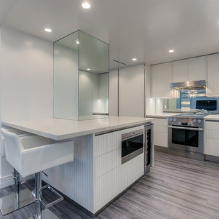 Inspiration for a mid-sized modern l-shaped eat-in kitchen in Los Angeles with a drop-in sink, louvered cabinets, stainless steel appliances and vinyl floors.