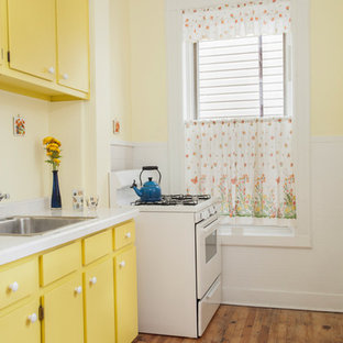 Inspiration for a small midcentury galley separate kitchen in New York with a drop-in sink, flat-panel cabinets, yellow cabinets, tile benchtops, yellow splashback, porcelain splashback, white appliances, light hardwood floors and no island.